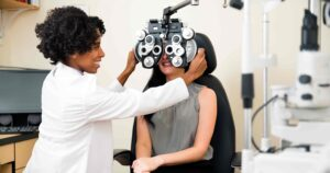 Woman getting her eyes examined by her optometrist for national eye exam month