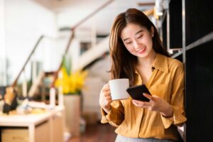 Young female holding coffee cup and smiling at phone